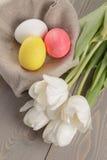 Pastelkleurpaaseieren met tulpen op lijst Royalty-vrije Stock Foto's