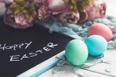 Pastelkleurpaaseieren op witte houten raad met bord met Gelukkige Pasen-inschrijving Royalty-vrije Stock Foto