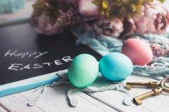 Pastelkleurpaaseieren op witte houten raad met bord met Gelukkige Pasen-inschrijving Royalty-vrije Stock Fotografie