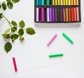 Pastell, Bleistifte, Papier und rosafarbene Blumen gesetzt auf weißen Tabellenschreibtisch, Draufsicht, Ebenenlage Lizenzfreie Stockbilder