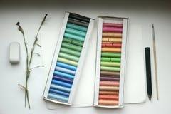 Pastell, borste, radergummi och blyertspenna på papperet Arkivfoto