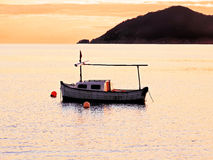 Pastell colored image showing a fisher boat. At sunset with lens flare and swimming stock photo