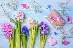 Pastell farbige Blumen und eine Geschenkbox Stockbilder