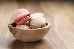 Pastell farbige macarons mit Erdbeer-, Rosafarbenem und Karamellaroma in der hölzernen Schüssel Stockbilder