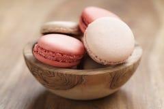 Pastell farbige macarons mit Erdbeer-, Rosafarbenem und Karamellaroma in der hölzernen Schüssel Lizenzfreies Stockbild