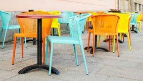Pastell farbige Stühle auf einem Straßencafé lizenzfreie stockbilder