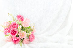 Pastell färbte künstliche rosa Rose auf weißem Pelzhintergrund Stockfoto