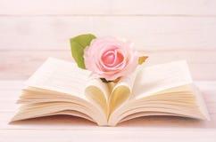 Pastell-Rose und geöffnetes Buch mit Herzform in der mittleren Seite stockfoto
