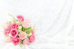 Pastellfärgad färgad konstgjord rosa färgros på vit pälsbakgrund Arkivfoto