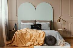 Pastellfärgad huvudgavel av konungformatsäng med hemtrevlig sängkläder och kuddar royaltyfri fotografi