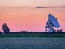 Pastellfärgad solnedgång över radiotelescopeantennen Arkivfoto