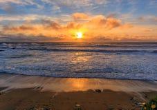 Pastellfärgade färger av solnedgången och silkeslent vatten från lång exponering av vågor som kraschar vid duvapunktfyren på nord arkivbilder