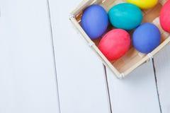 Pastellfärgade och färgrika easter ägg i korg lyckliga easter Arkivfoto