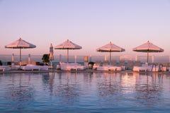Pastellfärgat solnedgångljus över simbassäng- och solsängar fotografering för bildbyråer