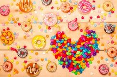 Pastellfarbe der süßen Schaumgummiringe mit Herzen formte auf hölzernen Hintergrund Lizenzfreies Stockbild