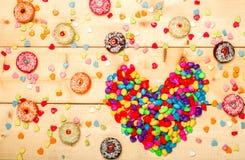 Pastellfarbe der süßen Schaumgummiringe mit Herzen formte auf hölzernen Hintergrund Stockfotos