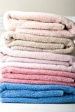 Pastellfarbenstapel Tücher auf einer Tabelle Stockbilder