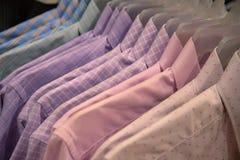 Pastellhemden auf hängt für Verkauf im Geschäft Formelle Kleidung auf Plastikaufhänger Offizielle Abnutzung für Männer im Kaufhau stockbilder