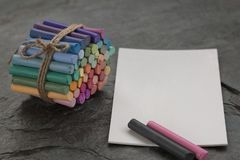Pastelli pastelli colorati con la carta bianca dell'acquerello su fondo di pietra scuro fotografia stock