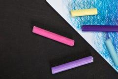 Pastelli colorati dei pastelli ed immagine colorata su un fondo scuro Fotografie Stock