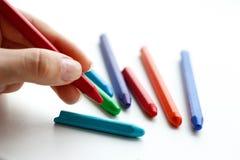 Pastelli colorati tenuta della mano Isolato su una priorità bassa bianca Cl Fotografie Stock
