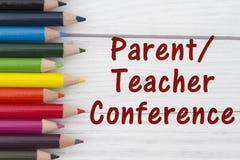Pastelli della matita con la conferenza dell'Genitore-insegnante del testo immagini stock