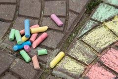 Pastelli e disegni di gesso Colourful sulla pavimentazione/asfalto immagini stock