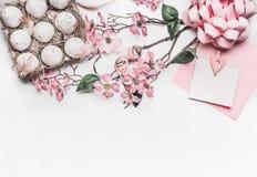 Pastellrosa Ostern-Grußkartenspott oben mit Blütendekoration, Federn, Eier im Kartonkasten auf weißem Schreibtischhintergrund, Dr Lizenzfreies Stockfoto