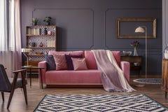 Pastelowych menchii koc na dopasowywanie kanapie w żywym izbowym wnętrzu w zdjęcie royalty free