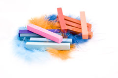 Pastels with plumage. Blue, red and pink square pastel crayons on plumage background Stock Photography