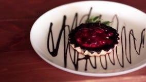 Pasticceria deliziosa con le bacche su un piatto decorato con la salsa di cioccolato archivi video