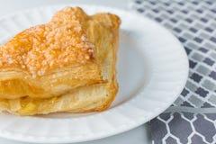 Pasticceria di calzone alle mele sul piatto con fondo ed il panno bianchi Fotografia Stock