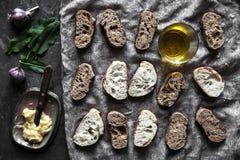 Pasticceria francese, baguette su un fondo nero con i dettagli per cucinare immagini stock