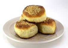 Pasticcerie casalinghe, panini rubicondi con i semi di sesamo su un piatto della perla su un fondo bianco fotografia stock