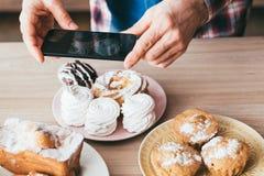 Pasticcerie fresche dello smartphone dell'uomo del dessert di blogger dell'alimento fotografie stock libere da diritti