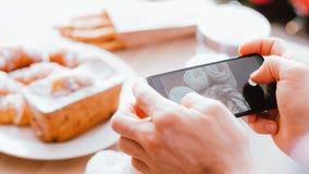 Pasticcerie fresche dello smartphone dell'uomo del dessert di blogger dell'alimento fotografia stock libera da diritti