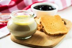 Pasticcio di fegato del pollo in un barattolo di vetro ed in un pane tostato fotografia stock