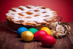 Pastiera. International Cuisine - Desserts - Neapolitan Pastiera and colorful Easter eggs. Pastiera is a wheat and ricotta pie that is also known as Pizza Gran Royalty Free Stock Photography