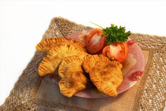 Pasties on the Caucasus. Pasties with meat lying on a plate isolated on a light background Royalty Free Stock Photo