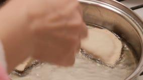 Pasties, cheburek, z mięsem smażącym w słonecznikowym oleju w smażyć nieckę W górę dziewczyny ręki w różowym rękawie zbiory wideo