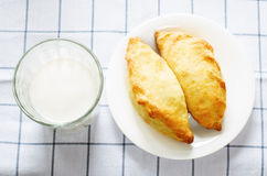 Pasties stuffed meat and glass of milk Stock Images