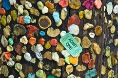 Pastilha elástica colada ao cargo de madeira com moeda de um centavo e bilhete Foto de Stock