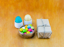 Pastilha elástica doce da cor pastel dos ovos em uma bacia e em um presente de madeira no papel de embalagem em um fundo de madei Fotos de Stock