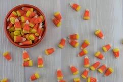 Pastillas de caramelo en cuenco anaranjado con derramamiento del lío encima foto de archivo
