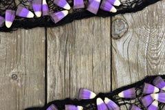 Pastillas de caramelo púrpuras de Halloween y marco negro del paño contra la madera imágenes de archivo libres de regalías