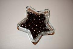Pastille de chocolat noir et sucré sur la cuvette en cristal Photos stock