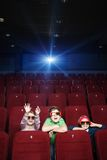Pastime at the cinema. Children spending time with pleasure in the movie theatre stock photography
