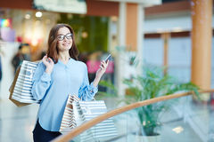 Pastime of shopaholic. Woman with gadget having happy pastime in the mall Royalty Free Stock Image