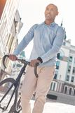 Traveling around. Young guy walking on city street with bicycle smiling happy Stock Photos