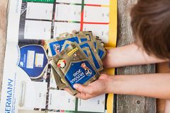 Pasting Panini stickers into album for 2018 championship. BERLIN, GERMANY - APRIL 20, 2018: Seven year old boy pasting stickers into the Panini collection album Stock Photos